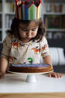 Portrait of little girl blowing out candle on her birthday cake at home - VABF03025