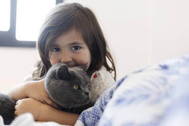 Portrait of little girl cuddling grey cat on bed - VABF03031