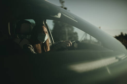Mid adult woman with protective mask in car - DMGF00093
