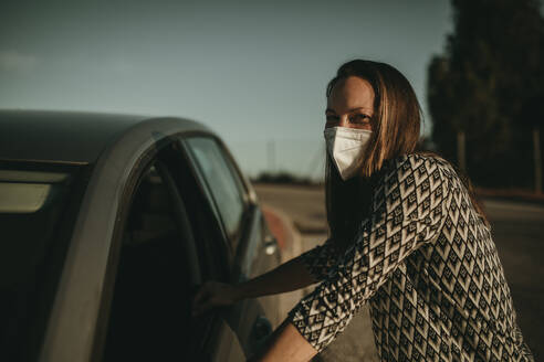 Mid adult woman with protective mask in car - DMGF00099