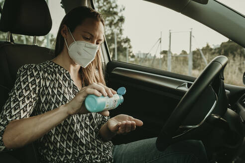 Mid adult woman with protective mask using sanitizer in car - DMGF00105