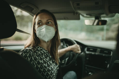 Mid adult woman with protective mask in car - DMGF00108