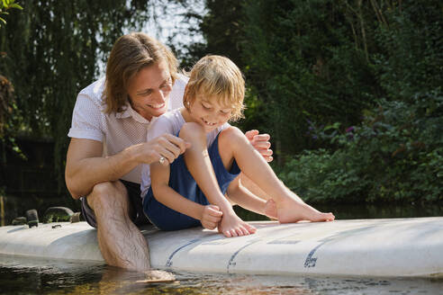 Happy father and son sitting on paddleboard in stream at forest - PWF00119