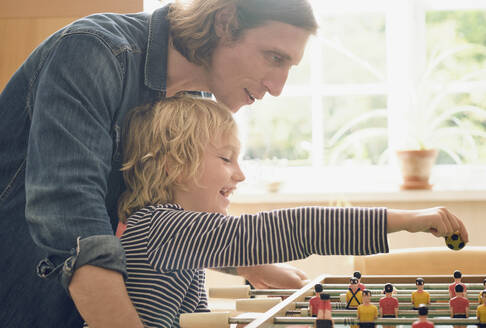 Father and son playing foosball at home - PWF00137