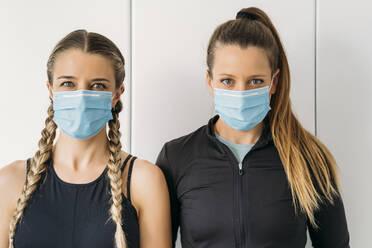 Portrait of two sporty women wearing face masks - MPPF00925