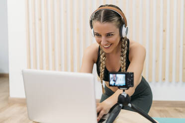 Sporty woman filming herself with camera and laptop - MPPF00946