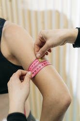 Measuring arm of sportswoman with tape measure - MPPF00955