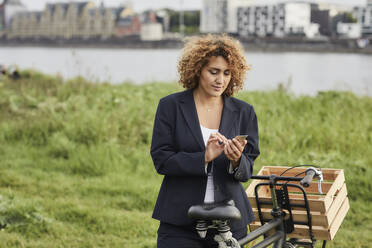 Businesswoman using smartphone at riverside in Cologne, Germany - MJFKF00339