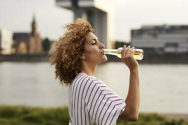 Portrait of smiling woman drinking from glass bottle at riverside - MJFKF00342