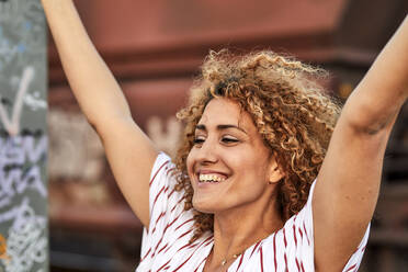 Portrait of smiling woman with raised arms - MJFKF00348