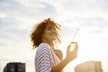 Portrait of smiling woman with glass bottle outdoors - MJFKF00354