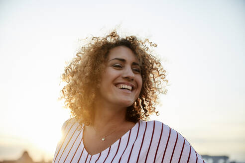 Portrait of smiling woman in the evening light - MJFKF00360