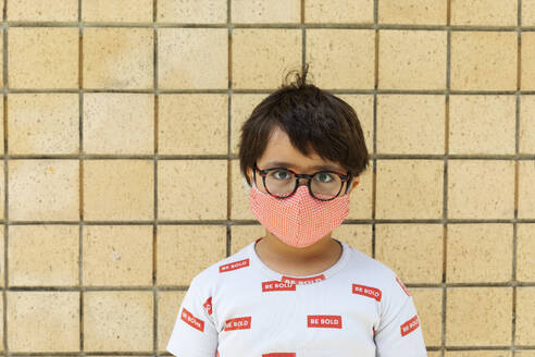 Boy wearing red mask in front of wall - VABF03044