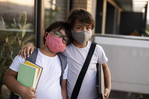 Siblings with books wearing masks outdoors - VABF03059
