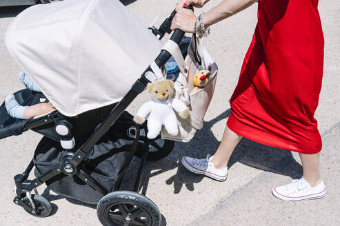 Mother pushing son in baby carriage while walking on street - JCMF00795