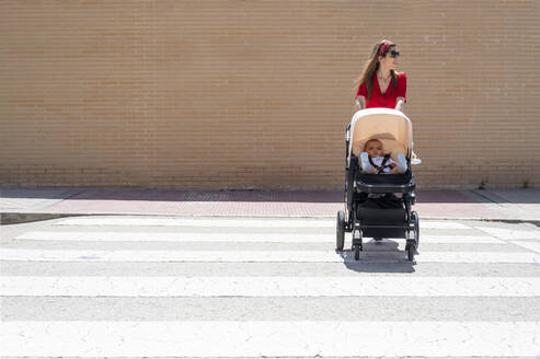 Mother wearing sunglasses pushing son in baby carriage while walking on street - JCMF00798