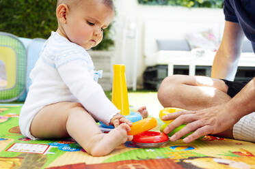 Father and cute son playing with toys while sitting at home - JCMF00807
