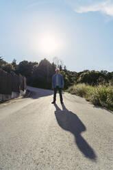 Senior man standing on road, shadow - AFVF06594