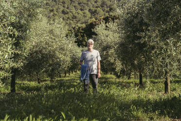 Senior man standing between row of trees on meadow - AFVF06597