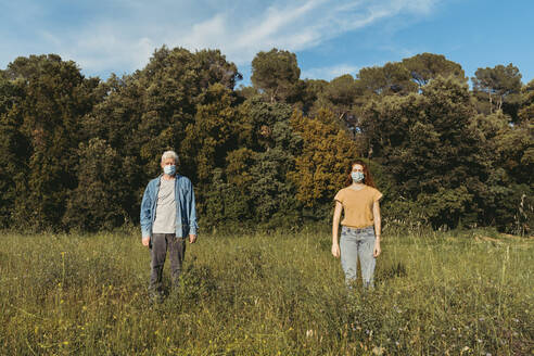 Woman and senior man with masks standing on meadow, safety distance - AFVF06600
