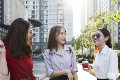 Female friends talking while standing against buildings in city - JPTF00519