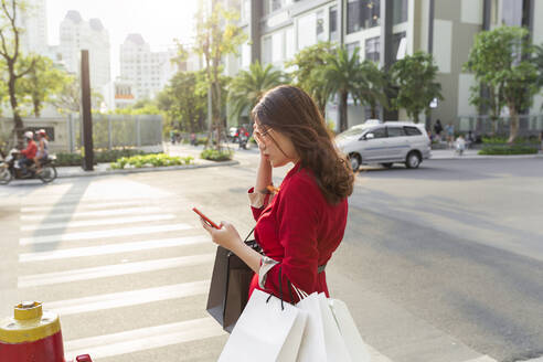 Young woman carrying shopping bags using smart phone while standing on street - JPTF00537