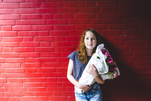 Girl holding bouquet while standing against red wall in city - IHF00340