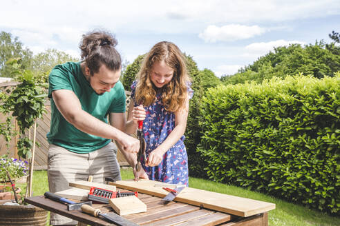 Young man helping sister in carpentry while standing at yard - IHF00343