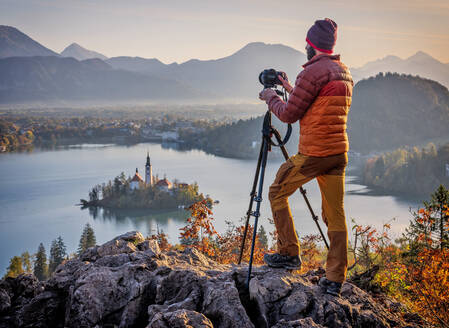 Slovenia, Upper Carniola, Bled, Man photographing Bled Island andPilgrimage Church of Assumption of Maria at foggy dawn - HAMF00635