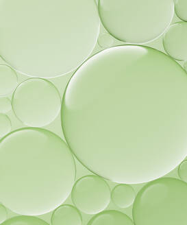 Three dimensional render of transparent glass spheres against green background - DRBF00170