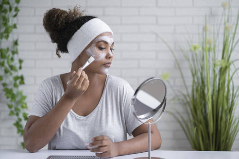 Woman wearing headband applying facial mask while looking in mirror at home - SNF00300