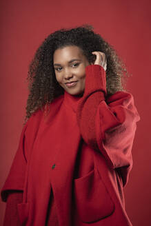 Smiling woman with curly hair wearing coat while standing against red background - SNF00312