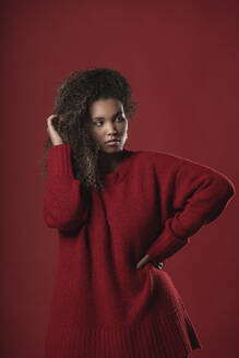 Serious thoughtful woman wearing sweater standing against red background - SNF00315