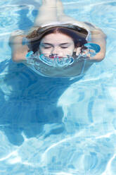 Close-up of young woman wearing eyes closed swimming in pool at tourist resort - JPTF00552