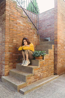 Sad thoughtful young woman sitting on steps by brick wall - AFVF06658