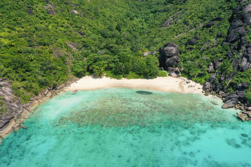 Aerial view of Anse di riz, Mahé, Seychelles. A boat drops tourists off at the beach, oblivious to the huge school of fish further down the shore. - AAEF08959