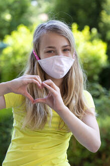 Close-up of girl wearing face mask forming heart shape with hands in park - JFEF00946
