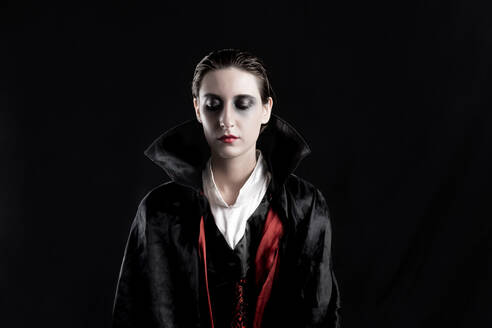 Young Woman In Vampire Costume During Halloween Against Black Background - EYF05373