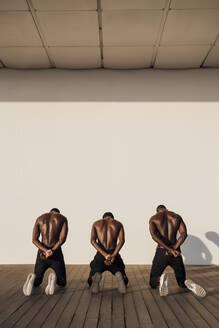 Three man crossing hands behind their backs, kneeling on planks - EGAF00169