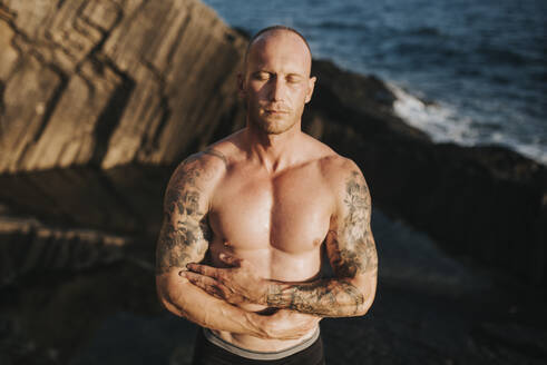 Tattooed nudist standing on volcanic rocks by the sea with arms crossed - MIMFF00047