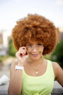Close-up of smiling woman with afro hair wearing sunglasses against sky - OCMF01360