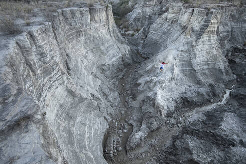 One man running down through a ridge at an old mining waste - CAVF84923
