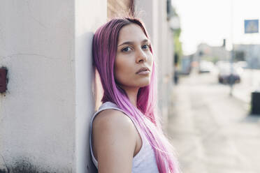 Portrait of a stylish young woman with pink hair leaning against a wall in the city - MEUF00780