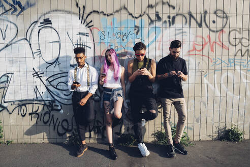 Group of friends using smartphones at a graffiti wall in the city - MEUF00786