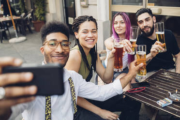 Happy friends holsing beer glasses and taking a selfie outdoors at a bar - MEUF00804