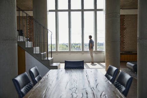 Wooden table in a loft flat with man at the window in background - MCF00931