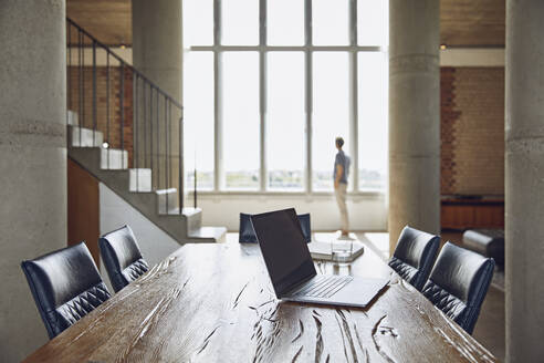 Laptop on wooden table in a loft flat with man at the window in background - MCF00934