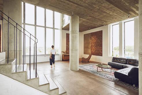 Woman walking in a loft flat - MCF01018