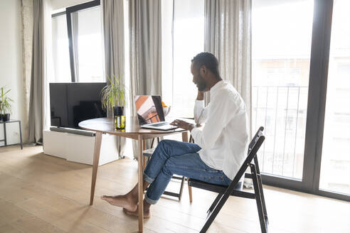 Man sitting at table in modern apartment using laptop - AHSF02732