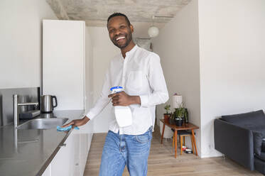 Portrait of laughing man standing in the kitchen cleaning countertop - AHSF02756